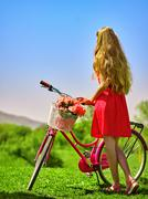 Girl wearing red polka dots dress rides bicycle into park. - stock photo
