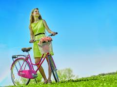 Girl wearing yellow polka dots dress rides bicycle into park. Stock Photos