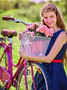 Girl wearing blue polka dots sundress rides bicycle with flowers basket. - stock photo