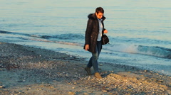 Woman in blue jeans collecting pebbles on the beach Stock Footage
