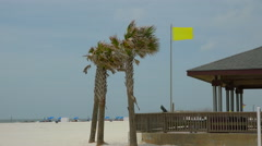 Yellow surf warning flag on Gulfport, AL beach Stock Footage