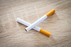 two cigarettes on a woody background - stock photo