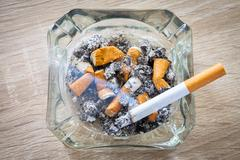 Burn cigarette in a full ashtray Stock Photos