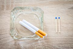 Cigarettes and matches on a woody background Stock Photos