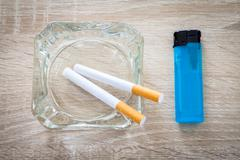 cigarettes in an ashtray with a lighter on a woody background - stock photo