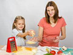 Six-year girl helps mother to rub grated cheese on pizza - stock photo