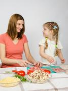 Little six year old girl joyful enthusiasm helps mum to prepare food Stock Photos