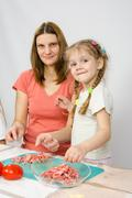 Little six year old girl helps mother to cook at the kitchen table Stock Photos