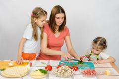 Two daughters are watching with interest as the mother chopped green - stock photo