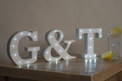 Dimly Illuminated Decorative Letters spelling Gin and Tonic G&T Stock Photos