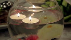 Burning candles floating in a decorative vase Stock Footage
