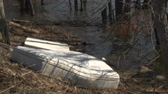 Mattress and Garbage on River Bank. Stock Footage