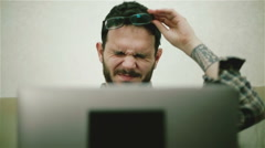 A tired man in glasses using a laptop - stock footage