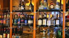 Liquor alcohol bottles displayed on shelves at the bar Stock Footage