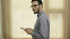A man in glasses using a tablet and rubbing his ear - stock footage