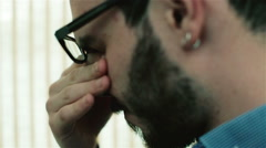 A man in glasses rubbing his eyes and talking Stock Footage