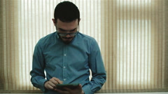 A man in glasses using a tablet Stock Footage