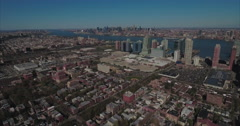 Aerials Flying Over Buildings Towards High Rises With Manhattan In The Distance Stock Footage