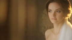 Gorgeous and fabulous brunette bride lit by golden sunset rays in the hotel room - stock footage