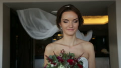 Happy gorgeous bride in luxury white dress with bouquet of flowers and long veil Stock Footage