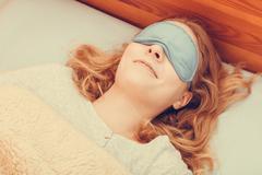 Sleeping woman wearing blindfold sleep mask. - stock photo