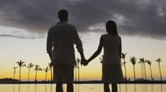 Romantic couple at sunset holding hands at beach walking hand in hand vacation Stock Footage