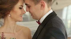 Groom gently kisses beautiful brunette bride close up. Camera movement in slow Stock Footage