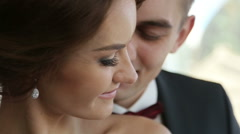 Groom gently touches beautiful face of his bride close up. Very tender moment - stock footage