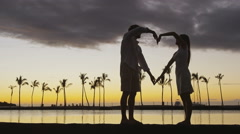 Couple at sunset forming heart shape with arms as romantic symbol of love - stock footage