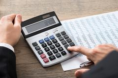Close-up Of A Businessman Analyzing Accounting Document With Calculator At De Stock Photos