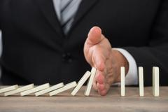 Close-up Of A Businessman Hand Stopping Dominoes From Falling On A Desk In Of - stock photo