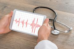 Close-up Of Male Doctor Showing Heartbeat On Digital Tablet With Stethoscope  Stock Photos