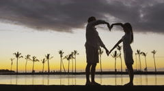 Romantic couple at sunset forming heart shape with arms as love symbol Stock Footage