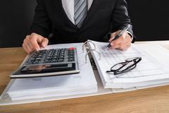 Close-up Of Young Male Accountant Working With Financial Data At Office Desk Stock Photos
