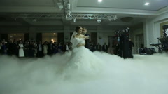 Happy newlyweds dancing waltz shrouded by white fume. Wonderful wedding party Stock Footage