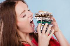 Woman taking eating pills tablets. Drug addict. - stock photo