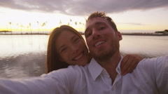 Couple romantic selfie video at sunset happy in love on beach Stock Footage