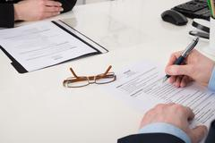 Close-up Of Businessperson Holding Pen Over Resume In Office Stock Photos