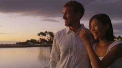 Honeymoon couple romantic at sunset walking in love enjoying vacation at night Stock Footage
