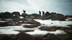 Climbers traverse boulders on mountain Stock Footage