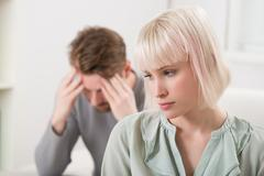 Sad Young Couple Having Argument At Home - stock photo