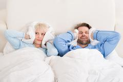 Young Unhappy Couple Covering Ears While Sleeping On Bed At Home - stock photo