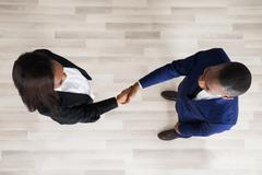 Elevated View Of Business Man And Woman Handshaking Stock Photos