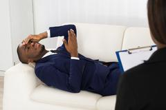 African American Man Laying On Couch In Front Of Psychiatrist With Clipboard Stock Photos