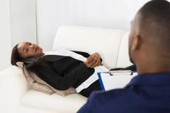 African American Woman Laying On Couch In Front Of Psychiatrist With Clipboar Stock Photos