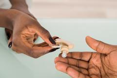 Close-up Of Doctor's Hand Giving Hearing Aid To Patient - stock photo