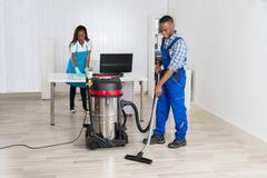 Young Male And Female Janitor Cleaning Office With Vacuum Cleaner Stock Photos