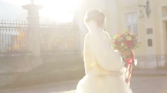 Gorgeous innocent brunette bride posing with wedding bouquet near baroque church - stock footage