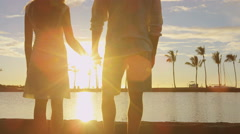 Honeymoon couple romantic at sunset holding hands in love enjoying vacation Stock Footage