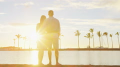 Romantic sunset happy couple in love enjoying summer vacation sunlight at beach - stock footage